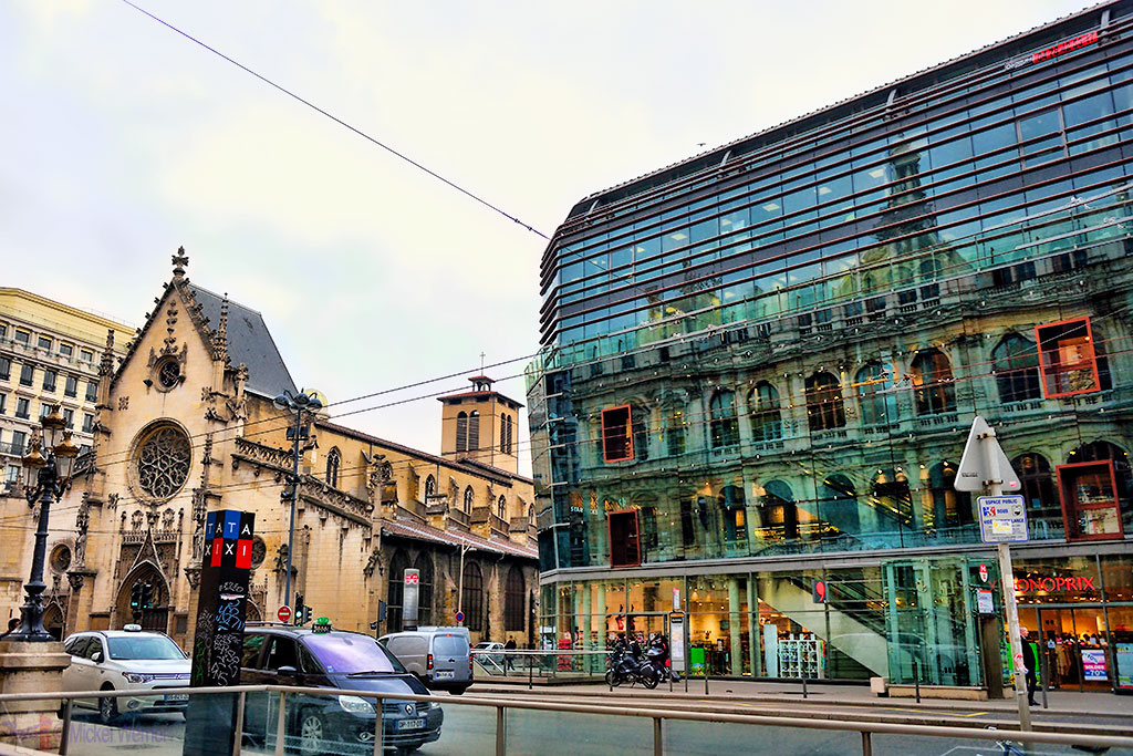 Reflection of the former commercial exchange (Palais de la Bourse) of Lyon in a small shopping centre and an old church